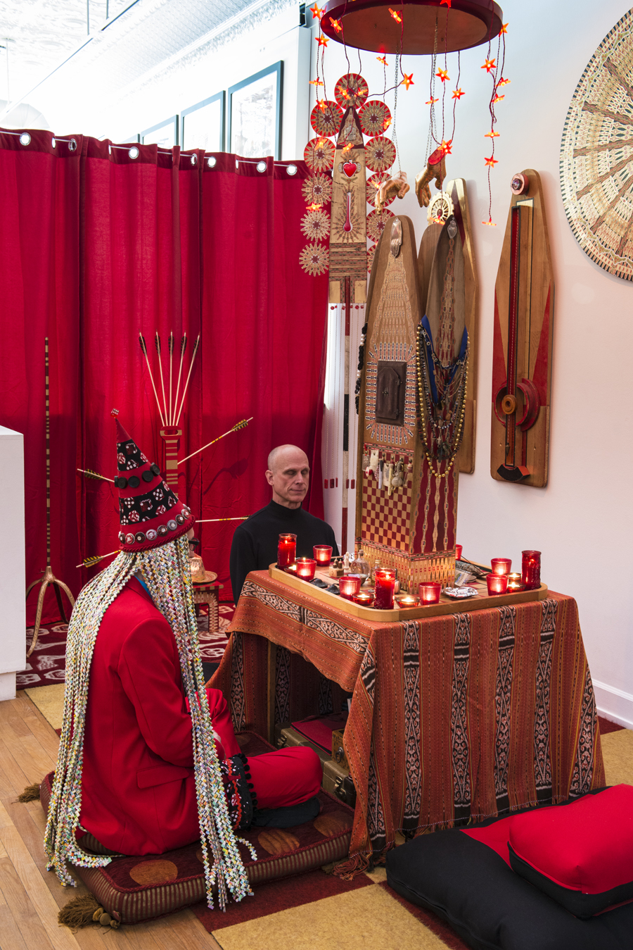 "Shaman Johnny sitting with a visitor in front of the ""Reliquary of Protection\"" in the meditation area."